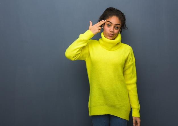 Jovem negra, fazendo um gesto de suicídio