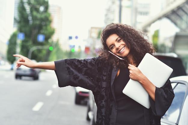 Jovem negra feliz tenta pegar um táxi na rua segurando um laptop