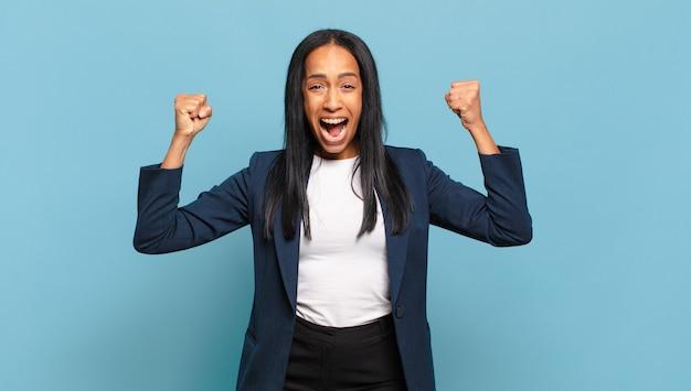 Jovem negra gritando agressivamente com uma expressão de raiva ou com os punhos cerrados celebrando o sucesso. conceito de negócios