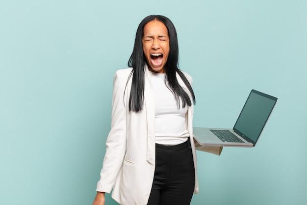 Jovem negra gritando agressivamente, parecendo muito zangada, frustrada, indignada ou irritada, gritando não. conceito de laptop