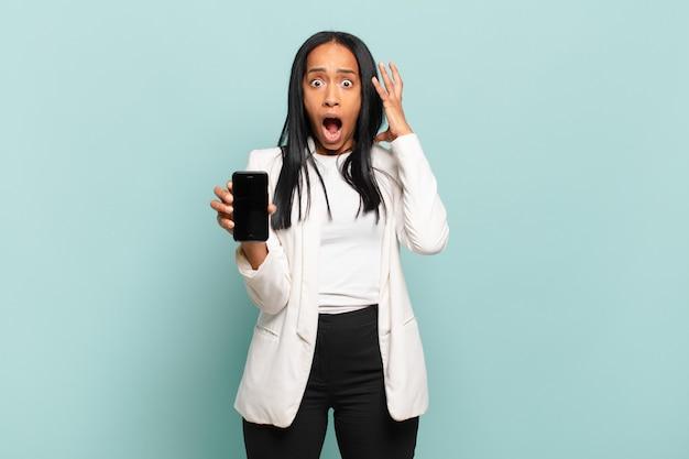 Jovem negra gritando com as mãos ao alto, sentindo-se furiosa, frustrada, estressada e chateada. conceito de telefone inteligente
