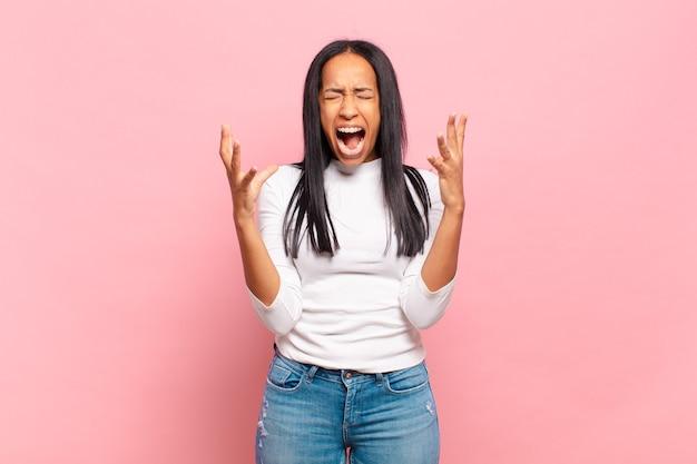 Jovem negra gritando furiosamente, sentindo-se estressada e irritada com as mãos para o alto dizendo por que eu