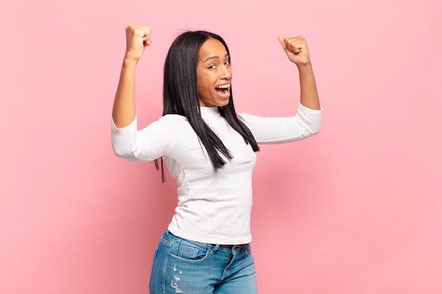 Jovem negra gritando triunfantemente, parecendo vencedora animada, feliz e surpresa, comemorando