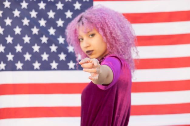 Jovem negra isolada em uma bandeira dos estados unidos, apontando para você lutando pela igualdade de raça
