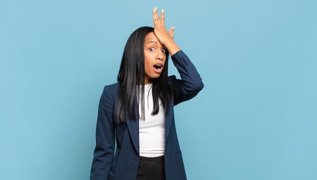 Jovem negra levantando a palma da mão na testa pensando oops
