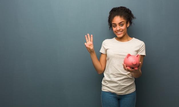 Jovem negra mostrando o número três. ela está segurando um cofrinho.