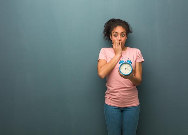 Jovem negra muito assustada e com medo escondida. ela está segurando um despertador.