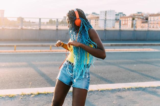 Jovem negra mulher milenar ao ar livre escutando música dançando