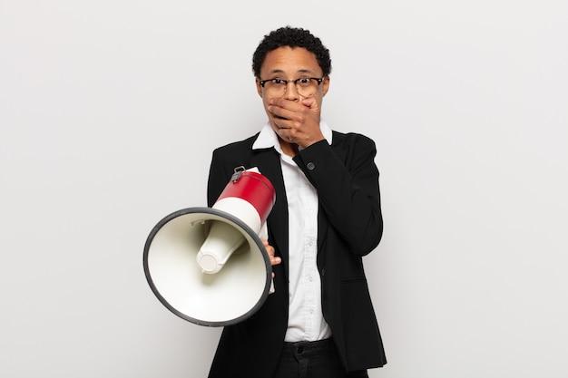 Jovem negra negra cobrindo a boca com as mãos com uma expressão chocada e surpresa, mantendo um segredo ou dizendo oops