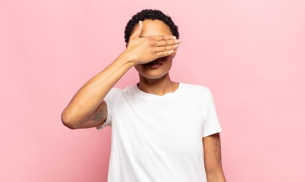 Jovem negra negra cobrindo os olhos com uma das mãos sentindo-se assustada ou ansiosa, imaginando ou cegamente esperando por uma surpresa