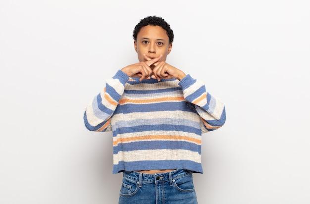 Jovem negra negra parecendo séria e descontente com os dois dedos cruzados em rejeição