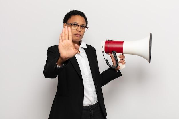 Jovem negra negra parecendo séria, severa, descontente e irritada mostrando a palma da mão aberta fazendo gesto de pare