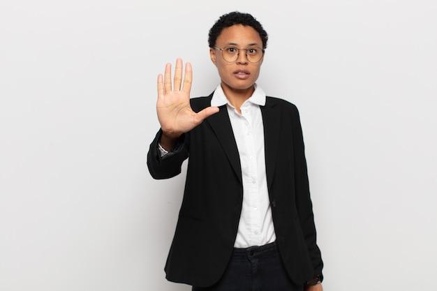 Jovem negra negra parecendo séria, severa, descontente e irritada, mostrando a palma da mão aberta fazendo gesto de pare