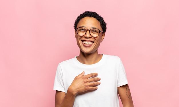 Jovem negra negra rindo alto de uma piada hilária, sentindo-se feliz e alegre, se divertindo