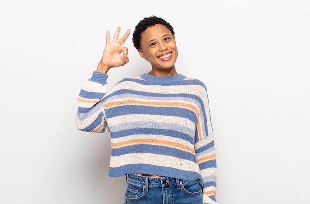 Jovem negra negra se sentindo feliz, pasma, satisfeita e surpresa, mostrando gestos de ok e polegar para cima, sorrindo