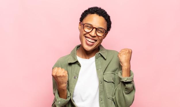 Jovem negra negra se sentindo feliz, surpresa e orgulhosa, gritando e comemorando o sucesso com um grande sorriso