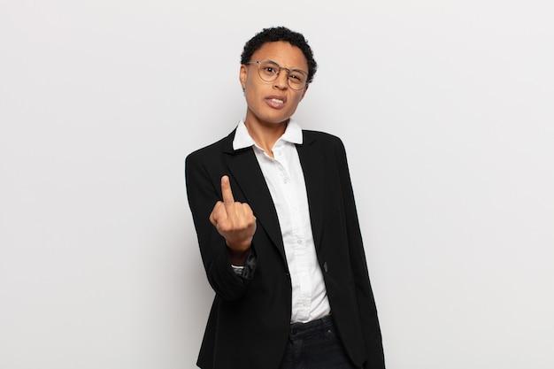 Jovem negra negra se sentindo irritada, irritada, rebelde e agressiva, sacudindo o dedo do meio e revidando