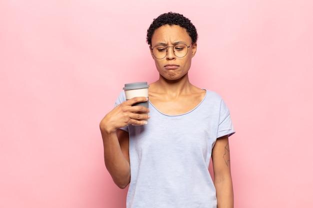 Jovem negra negra se sentindo triste, chateada ou com raiva e olhando para o lado com uma atitude negativa, franzindo a testa em desacordo