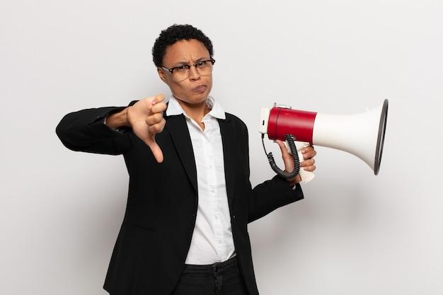 Jovem negra negra se sentindo zangada, irritada, decepcionada ou descontente, mostrando o polegar para baixo com um olhar sério