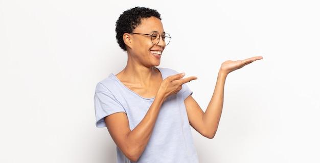 Jovem negra negra sorrindo alegremente e apontando para copiar o espaço na palma da mão ao lado, mostrando ou anunciando um objeto
