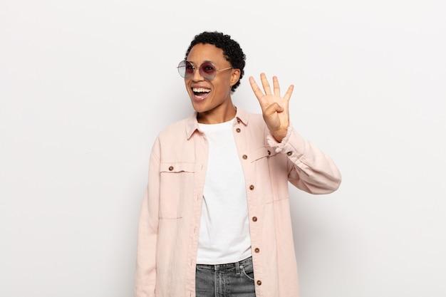 Jovem negra negra sorrindo e parecendo amigável, mostrando o número quatro ou o quarto com a mão para a frente, em contagem regressiva
