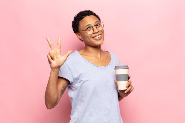 Jovem negra negra sorrindo e parecendo amigável, mostrando o número três ou o terceiro com a mão para a frente, em contagem regressiva