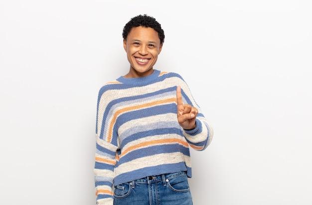 Jovem negra negra sorrindo e parecendo amigável, mostrando o número um ou primeiro com a mão para a frente, em contagem regressiva