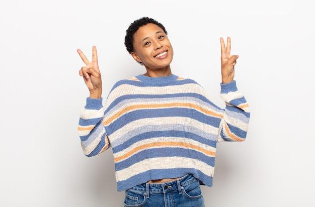 Jovem negra negra sorrindo e parecendo feliz, despreocupada e positiva, gesticulando vitória ou paz com uma das mãos