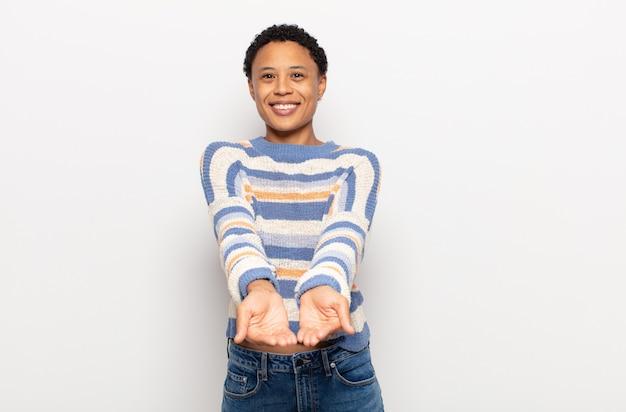 Jovem negra negra sorrindo feliz com um olhar amigável, confiante e positivo, oferecendo e mostrando um objeto ou conceito