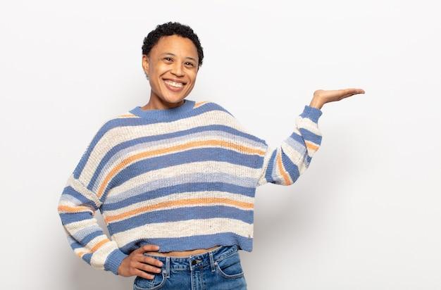 Jovem negra negra sorrindo, sentindo-se confiante, bem-sucedida e feliz, mostrando conceito ou ideia no espaço da cópia ao lado