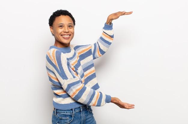 Jovem negra negra sorrindo, sentindo-se feliz, positiva e satisfeita, segurando ou mostrando um objeto ou conceito no espaço da cópia