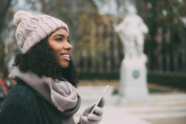 Jovem negra no telefone celular perto do palácio real no inverno