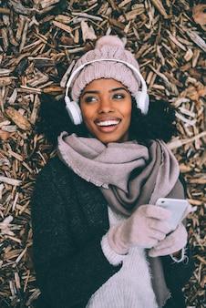Jovem negra no telefone móvel deitado sobre pedaços de madeira