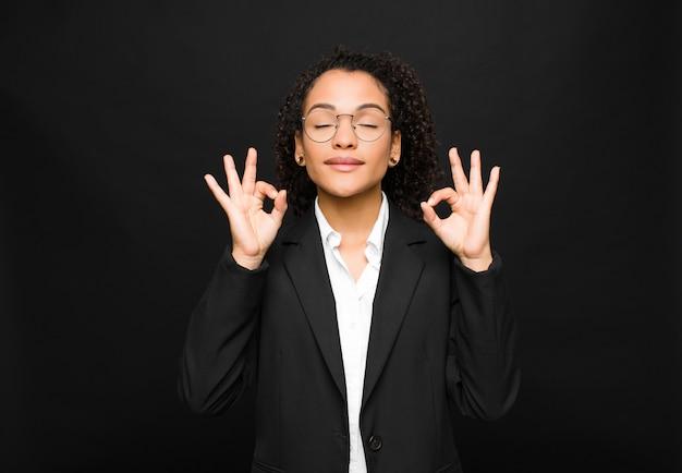 Jovem negra olhando concentrada e meditando, sentindo-se satisfeita e relaxada, pensando ou fazendo uma escolha contra a parede preta