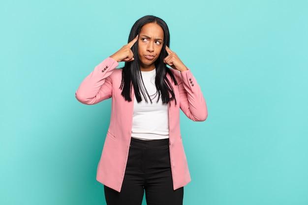 Jovem negra olhando concentrada e pensando seriamente em uma ideia, imaginando uma solução para um desafio ou problema. conceito de negócios