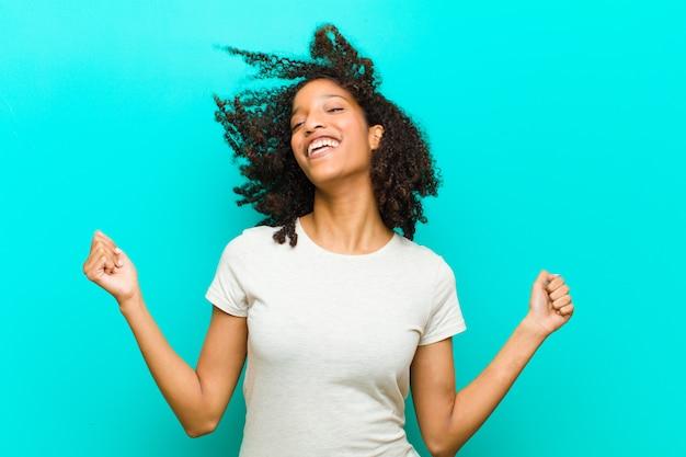 Jovem negra olhando extremamente feliz e surpresa, comemorando o sucesso, gritando e pulando contra a parede azul