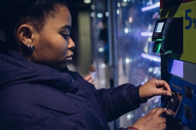 Jovem negra olhando máquina automática