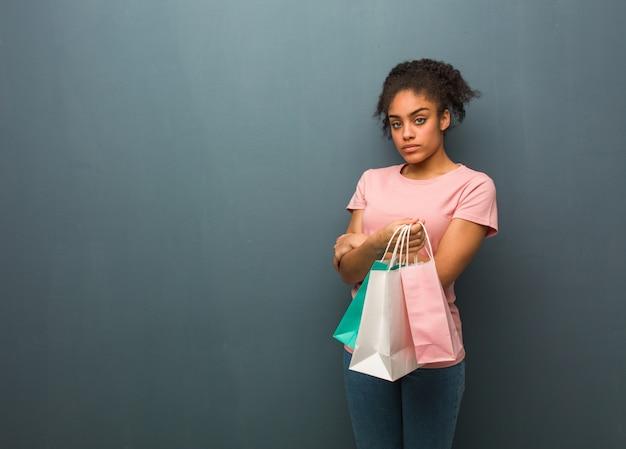 Jovem negra, olhando para a frente. ela está segurando uma sacola de compras.