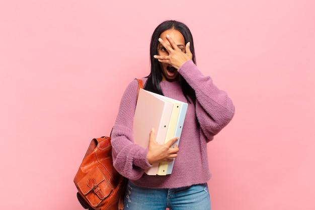 Jovem negra parecendo chocada, assustada ou apavorada, cobrindo o rosto com a mão e espiando por entre os dedos. conceito de estudante