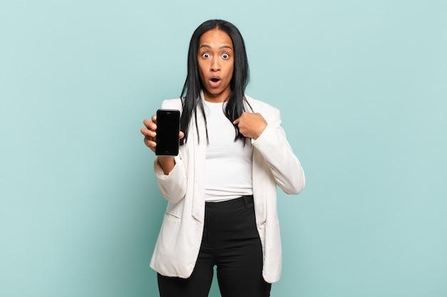 Jovem negra parecendo chocada e surpresa com a boca aberta, apontando para si mesma. conceito de telefone inteligente