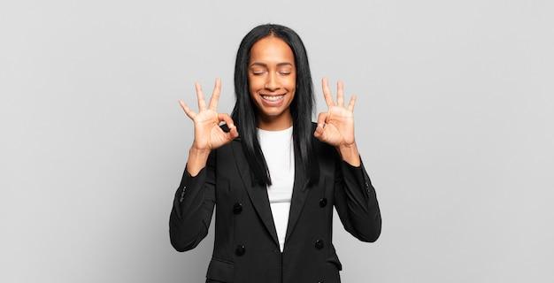 Jovem negra parecendo concentrada e meditando, sentindo-se satisfeita e relaxada, pensando ou fazendo uma escolha. conceito de negócios