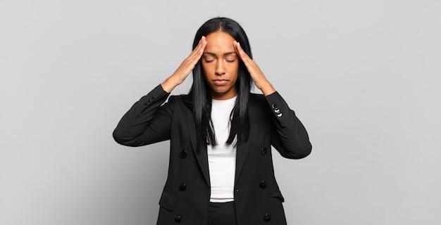 Jovem negra parecendo concentrada, pensativa e inspirada, fazendo um brainstorming e imaginando com as mãos na testa. conceito de negócios