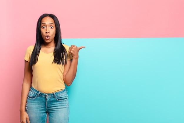 Jovem negra parecendo espantada em descrença, apontando para o objeto ao lado e dizendo uau, inacreditável. copie o conceito de espaço