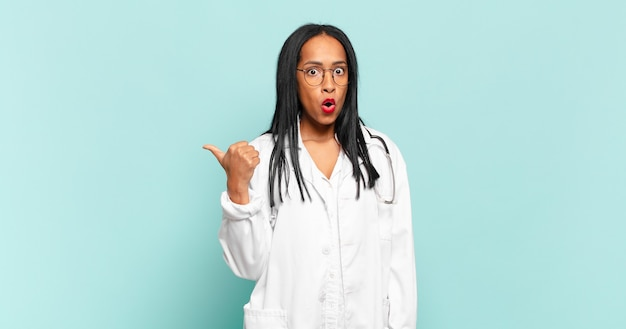 Jovem negra parecendo espantada em descrença, apontando para um objeto ao lado e dizendo uau, inacreditável. conceito de médico