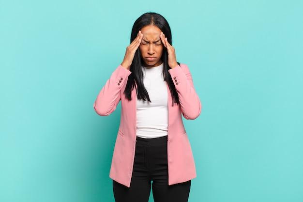 Jovem negra parecendo estressada e frustrada, trabalhando sob pressão, com dor de cabeça e preocupada com problemas