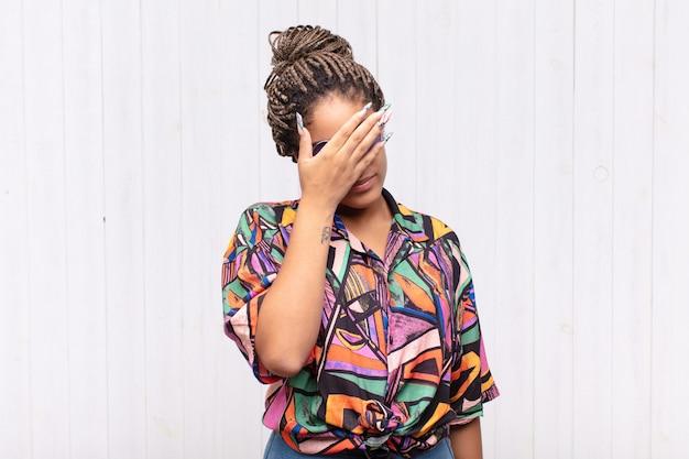 Jovem negra parecendo estressada, envergonhada ou chateada, com dor de cabeça, cobrindo o rosto com a mão