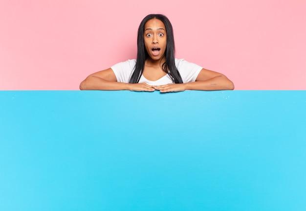 Jovem negra parecendo muito chocada ou surpresa, olhando com a boca aberta dizendo uau. copie o conceito de espaço