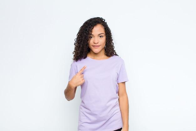 Jovem negra parecendo orgulhosa, confiante e feliz, sorrindo e apontando para si mesma ou fazendo o sinal de número um na parede branca
