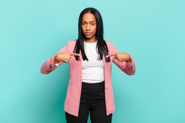 Jovem negra parecendo orgulhosa, positiva e casual, apontando para o peito com as duas mãos. conceito de negócios