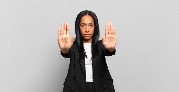 Jovem negra parecendo séria, infeliz, irritada e descontente, proibindo a entrada ou dizendo pare com as palmas das mãos abertas. conceito de negócios